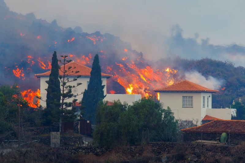 Lava flows behind a house following the eruption of a volcano in Spain