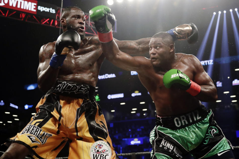 FILE - In this March 3, 2018, file photo, Deontay Wilder, left, and Luis Ortiz trade punches during the third round of a WBC heavyweight championship bout in New York. Wilder is awkward but dangerous, a string bean of a heavyweight with a crushing right hand that can change everything in a fraction of a second. Luis Ortiz is a big puncher, too, though there are questions about both his stamina and age going into Saturdays rematch with Wilder that serves as an appetizer for what comes next. (AP Photo/Frank Franklin II, File