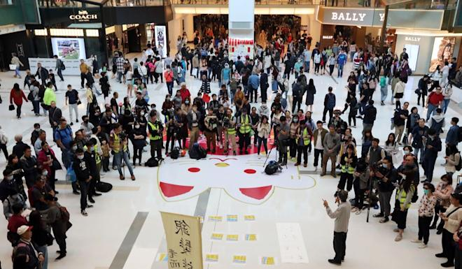 Protesters put up posters and giving out fliers at the New Town Plaza in Sha Tin. Photo: Felix Wong