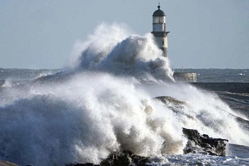 Waves crash against the pier wall at Seaham Lighthouse on the County Durham coast: PA