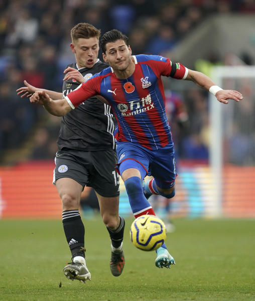 Leicester City's Harvey Barnes, left, and Crystal Palace's Joel Ward battle for the ball during the English Premier League soccer match at Selhurst Park, London, Sunday Nov. 3, 2019. (John Walton/PA via AP)