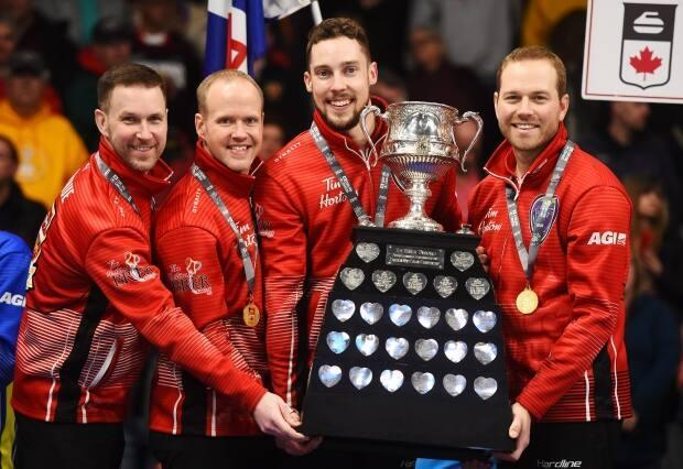 Team Newfoundland and Labrador skip Brad Gushue, left to right, third Mark Nichols, second Brett Gallant and lead Geoff Walker hold the Brier Tankard trophy after defeating Team Alberta in the 2020 Brier curling final.