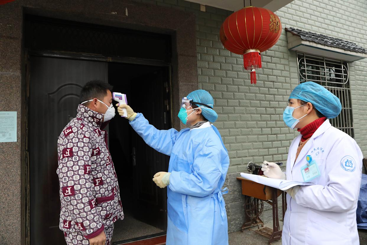 HANGZHOU, CHINA - JANUARY 27 2020: Community health workers check the body temperature of a villager returning from Hubei province in Hangzhou in east China's Zhejiang province Monday, Jan. 27, 2020. Governments outside Hubei province have put tens of thousands of people who had stayed in Hubei in the past weeks into home quarantine for health observations.- PHOTOGRAPH BY Feature China / Barcroft Media (Photo credit should read Feature China/Barcroft Media via Getty Images)