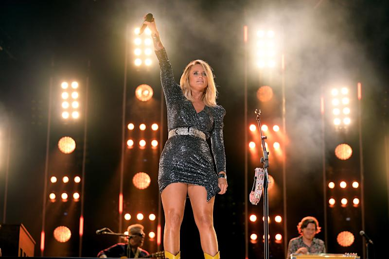 Miranda Lambert stands on stage holding her microphone in the air