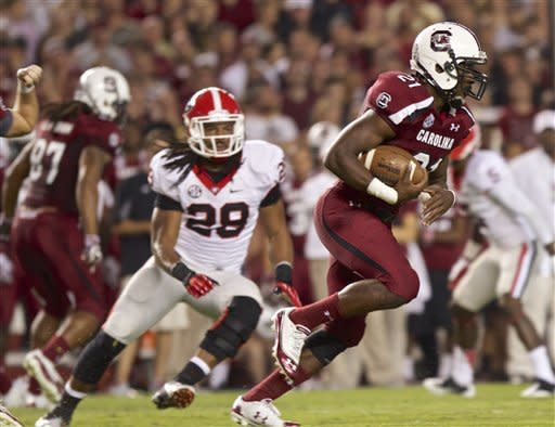 South Carolina running back Marcus Lattimore, right, breaks through the Georgia defensive line to pick up a first down as Georgia outside linebacker Jarvis Jones (29) pursues during the first quarter of an NCAA college football game in Columbia, S.C., Saturday, Oct. 6, 2012. (AP Photo/Brett Flashnick)