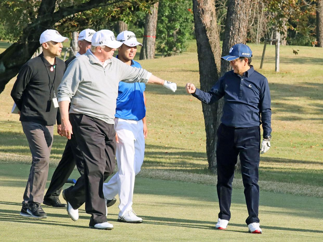President Donald Trump gestures to Japan's Prime Minister Shinzo Abe as Japanese professional golfer Hideki Matsuyama looks on, as they play golf at the Kasumigaseki Country Club in Kawagoe, north of Tokyo, Japan.