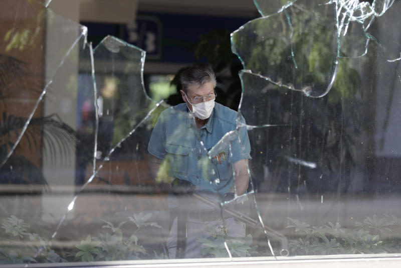 A worker vacuums broken glass from store front in downtown Louisville, Ky. , Saturday, May 30, 2020. The store was damaged Friday evening during a protest over the deaths of George Floyd and Breonna Taylor. (AP Photo/Darron Cummings)