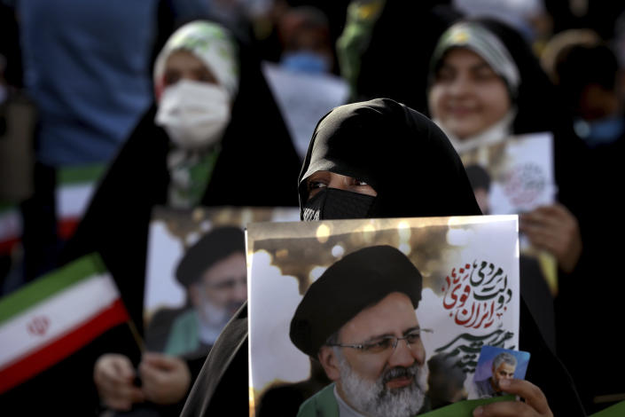 A supporter of presidential candidate Ebrahim Raisi holds a sign during a rally in Tehran, Iran, Wednesday, June 16, 2021. Iran's clerical vetting committee has allowed just seven candidates for the Friday, June 18, ballot, nixing prominent reformists and key allies of President Hassan Rouhani. The presumed front-runner has become Ebrahim Raisi, the country's hard-line judiciary chief who is closely aligned with Supreme Leader Ayatollah Ali Khamenei. (AP Photo/Ebrahim Noroozi)