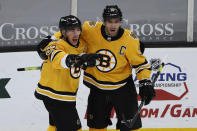 Boston Bruins' Patrice Bergeron, right, celebrates with Brad Marchand, left, after Marchand scored against the Pittsburgh Penguins during the second period of an NHL hockey game Saturday, April 3, 2021, in Boston. (AP Photo/Winslow Townson)