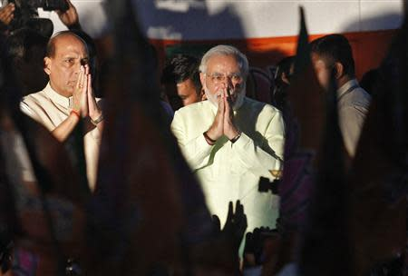 India's Hindu nationalist Narendra Modi (C) and Rajnath Singh (L), president of India's main opposition Bharatiya Janata Party (BJP), greet party supporters after Modi was crowned as the prime ministerial candidate for the BJP at the party headquarters in New Delhi September 13, 2013. REUTERS/Anindito Mukherjee