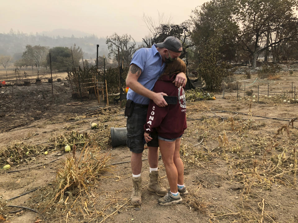 """Kevin Conant and his wife, Nikki, hug after looking at the debris of their burnt home and business """"Conants Wine Barrel Creations,"""" after the Glass/Shady fire completely engulfed it, Wednesday, Sept. 30, 2020, in Santa Rosa, Calif. The Conants escaped with their lives, which we are grateful for, but they barely made it out with the clothes on their backs in the wake of the fire. The Glass and Zogg fires are among nearly 30 wildfires burning in California. (AP Photo/Haven Daley)"""