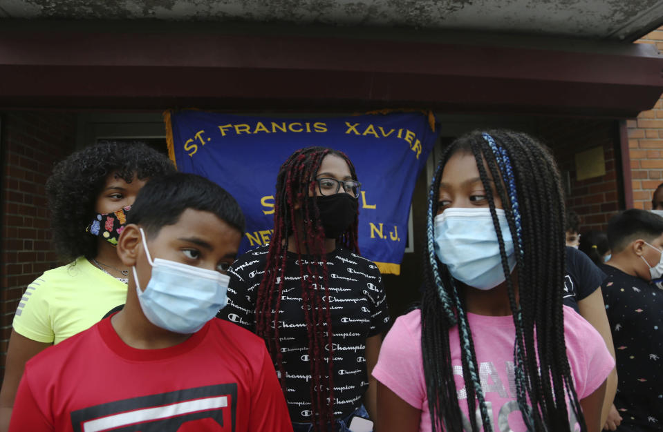 FILE - In this Thursday, Aug. 6, 2020 file photo, Malik Bey, 11, left, stands with his sisters in front of St. Francis Xavier School in Newark, as parents meet to fight the school's permanent closure. Amid the pandemic, more than 200 schools closed for good, and enrollment at the 5,981 remaining schools fell by 6.4% -- or more than 111,000 students – for the 2020-2021 academic year, according to the National Catholic Educational Association. (AP Photo/Jessie Wardarski)