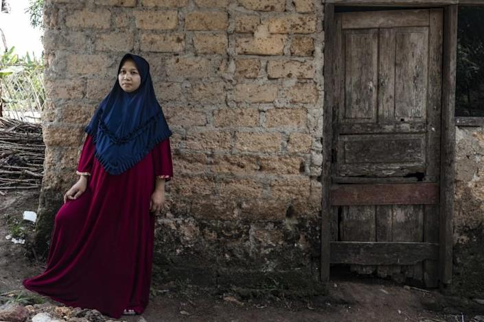 """Sri Siti Marni, 25, waits for her husband to come home from work at a nearby field in Bogor, Indonesia. """" I used to travel around Jakarta by myself. After being imprisoned for so long, I feel like I want to see everything"""", she said. Irene Barlian for The Los Angeles Times."""