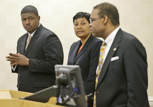 CORRECTS SCHOOL TO VIRGINIA STATE UNIVERSITY, NOT NORFOLK STATE UNIVERSITY, AND LOCATION TO ETTRICK, NOT PETERSBURG - Virginia State University head football coach, Latrell Scott, left, and athletic director, Peggy Davis, center, listen as VSU president Keith T. Miller, right, address a press conference at Virginia State University in Ettrick, Va., Monday, Nov. 18, 2013. School officials held the press conference to answer questions after Winston-Salem quarterback Rudy Johnson was beaten in a bathroom brawl Friday, Nov. 15 that led to VSU being banned from post season play. (AP Photo/Steve Helber)