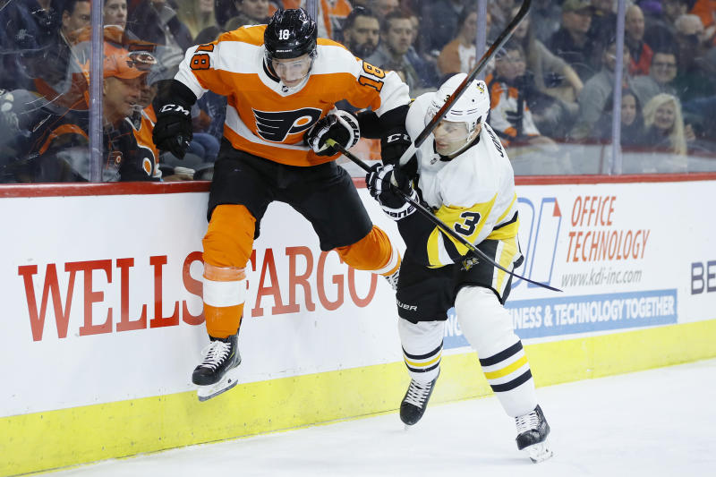 FILE - In this Jan. 21, 2020, file photo, Philadelphia Flyers' Tyler Pitlick, left, tries to jump past Pittsburgh Penguins' Jack Johnson during the second period of an NHL hockey game in Philadelphia. The latest chapter of The Battle of Alberta is on hold. So's the potential renewal of the Pennsylvania rivalry between the Penguins and Flyers. It's unclear when or if the coronvirus pandemic-delayed NHL playoffs -- which were supposed to begin Wednesday -- will be played or what form they'll resemble. (AP Photo/Matt Slocum, FIle)