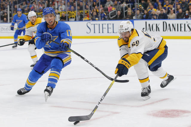 Nashville Predators' Roman Josi, right, of Switzerland, reaches for the puck as he is pressured by St. Louis Blues' Jaden Schwartz during the second period of an NHL hockey game Saturday, Feb. 15, 2020, in St. Louis. (AP Photo/Billy Hurst)