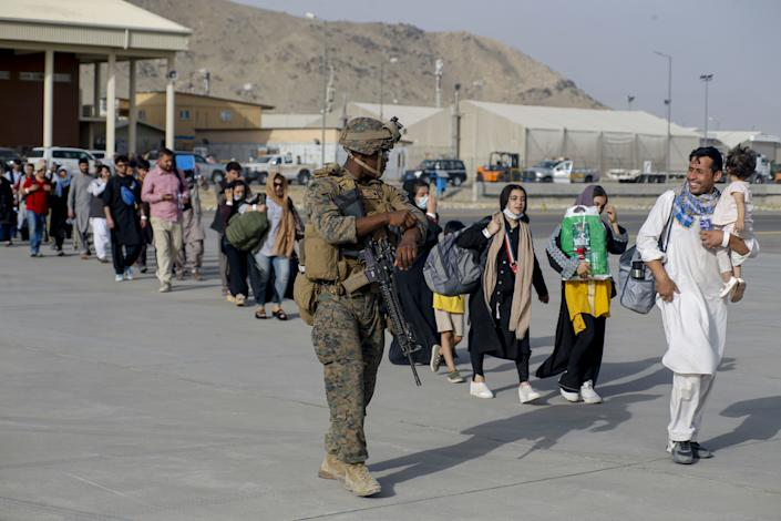 U.S. Marines assigned to 24th Marine Expeditionary Unit escorts evacuees during an evacuation at Hamid Karzai International Airport, Afghanistan, on August 18, 2021. (Lance Cpl Nicholas Guevara/USMC/UPI/Shutterstock)