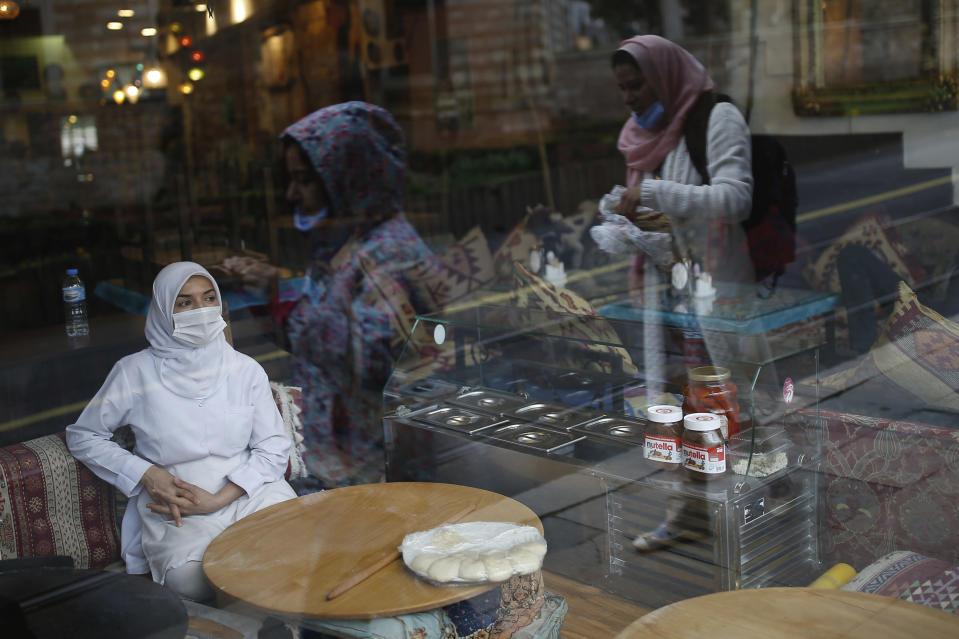 FILE - In this Wednesday, March 25, 2020, file photo, a customer wearing a protective mask due to the coronavirus outbreak, waits sits on a table of a restaurant, in central Istanbul. When Turkey changed the way it reports daily COVID-19 infections, it confirmed what medical groups and opposition parties have long suspected — that the country is faced with an alarming surge of cases that is fast exhausting the Turkish health system. The official daily COVID-19 deaths have also steadily risen to record numbers in a reversal of fortune for the country that had been praised for managing to keep fatalities low. With the new data, the country jumped from being one of the least-affected countries in Europe to one of the worst-hit.(AP Photo/Emrah Gurel, File)