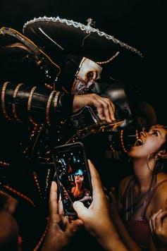 A smartphone in the foreground filming as a man in a costume pours liquor into a young woman's mouth