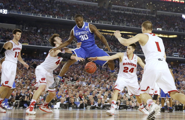 Kentucky forward Julius Randle (30) loses the ball as Wisconsin forward Frank Kaminsky (44), guard Bronson Koenig (24) and Ben Brust (1) defend during the first half of the NCAA Final Four tournament college basketball semifinal game Saturday, April 5, 2014, in Arlington, Texas. (AP Photo/Eric Gay)