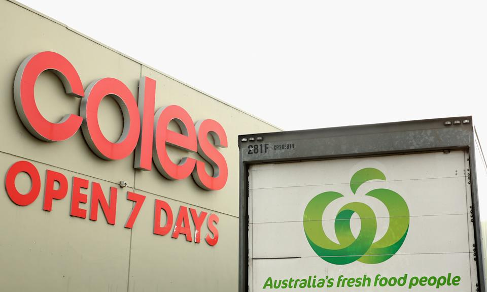 A Coles storefront with Woolworths truck parked outside.