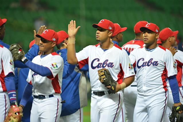 Cuba's infielder Jose Abreu (C) and his teammates high five each other after their winning game against China at the first-round Pool A game in the World Baseball Classic tournament in Fukuoka on March 4, 2013. Cuba beat China 12-0 with a called game at the seventh inning. AFP PHOTO / KAZUHIRO NOGIKAZUHIRO NOGI/AFP/Getty Images