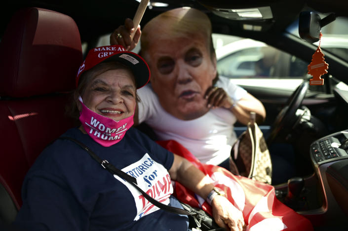 Former senator Miriam Ramírez de Ferrer poses for the camera flanked by a Trump cardboard cutout moments before leaving for the headquarters of the Republican party in support of President Donald Trump's candidacy a few weeks before the presidential election next November, in Carolina, Puerto Rico, Sunday, Oct. 18, 2020. President Donald Trump and former Vice President Joe Biden are targeting Puerto Rico in a way never seen before to gather the attention of tens of thousands of potential voters in the battleground state of Florida. (AP Photo/Carlos Giusti)