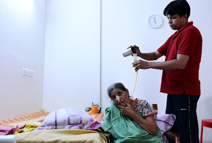62-year-old Indian woman Suresh Rani, given an overdose of sodium by doctors at a hospital which resulted in a permanent brain damage, is being fed through a tube by her son Rohit Goyal at their home in Noida, in New Delhi (AFP Photo/Sajjad Hussain)