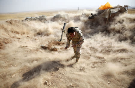 A Kurdish Peshmerga fighter launches mortar shells towards Zummar, controlled by Islamic State, near Mosul