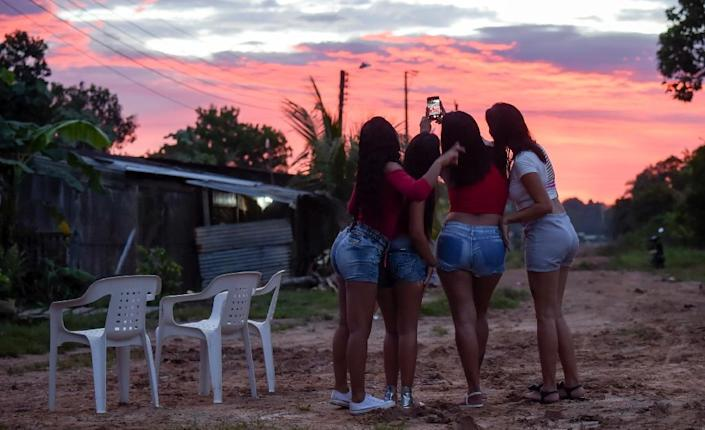 The Venezuelan women working as prostitutes in Calamar occasionally find a brighter moment -- here, they pose for a selfie outside the bar where they work (AFP Photo/Raul ARBOLEDA)