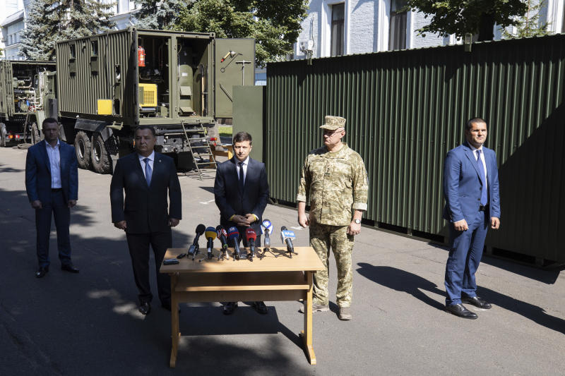 Ukrainian President Volodymyr Zelenskiy, center, speaks during the presentation new experimental military modular equipment for field in Kiev, Ukraine, Friday, July 19, 2019.Ukraine's president on Friday outlined the details of an impending prisoner swap with Russia, saying that Kiev is willing to release a jailed Russian journalist in exchange for a Ukrainian film director. (Ukrainian Presidential Press Office via AP)