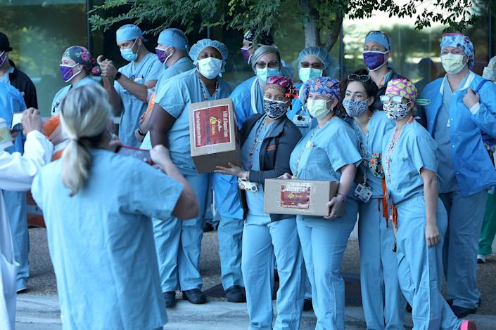 Nurses and doctors at UF Health Shands Cardiovascular Hospital present a photograph of boxes of masks donated by Bass Pro Shops to the Celebration Pointe Hospital in Gainesville, Florida, May 8, 2020. [Brad McClenny/The Gainesville Sun]
