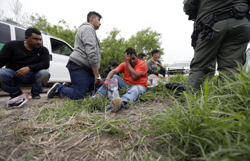 FILE - In this March 14, 2019, file photo, a Border Patrol agent talks with a group suspected of having entered the U.S. illegally near McAllen, Texas. A surge in family arrivals, largely from Guatemala and Honduras, has led Border Patrol agents to shift attention from preparing criminal cases to caring for children. (AP Photo/Eric Gay, File)