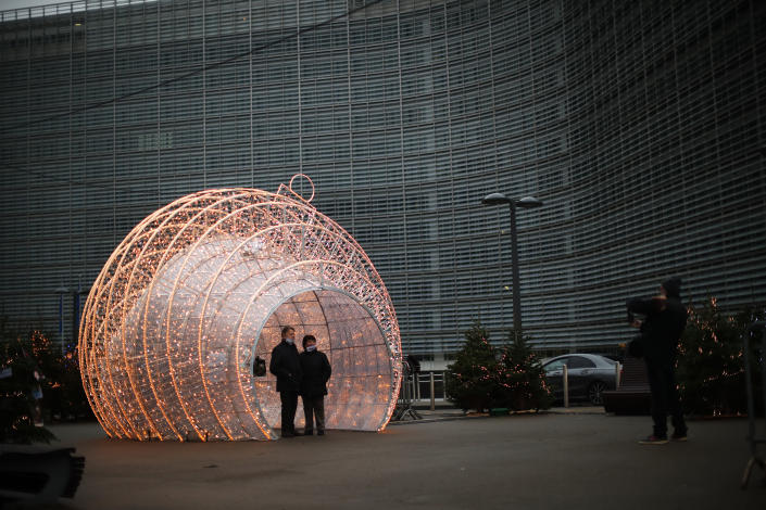 Passers by pose for a photograph next to Christmas decorations placed outside the European Commission headquarters in Brussels, Saturday, Dec. 12, 2020. British Prime Minister Boris Johnson and European Commission President Ursula von der Leyen have set a Sunday deadline to decide whether to keep talking or prepare all-out for a no-deal break. (AP Photo/Francisco Seco)