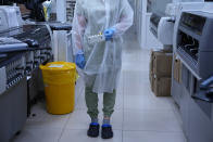 An employee holds a set of vials for analysis at the LabQuest laboratory, a clinic that does antibody testing and processing, in Moscow, Russia, Monday, July 12, 2021. In Russia, it's common to get an antibody test for the coronavirus and share the results. The tests are cheap, widely available and actively marketed by private clinics nationwide, and their use appears to be a factor in the country's low vaccination rate even as daily deaths and infections are rising again. (AP Photo/Alexander Zemlianichenko)