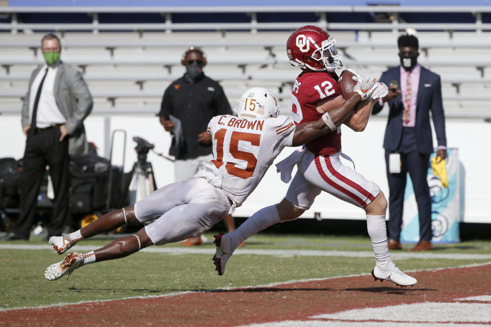 Oklahoma wide receiver Drake Stoops (12) scores the winning touchdown in overtime as Texas defensive back Chris Brown (15) tries to tackle him during an NCAA college football game in Dallas,Tx, Saturday, Oct. 10, 2020. Oklahoma defeated Texas 53-45 in four overtimes.(AP Photo/Michael Ainsworth)