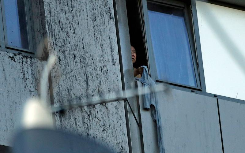 A person peers out of a window from the Grenfell Tower building - Credit: AP