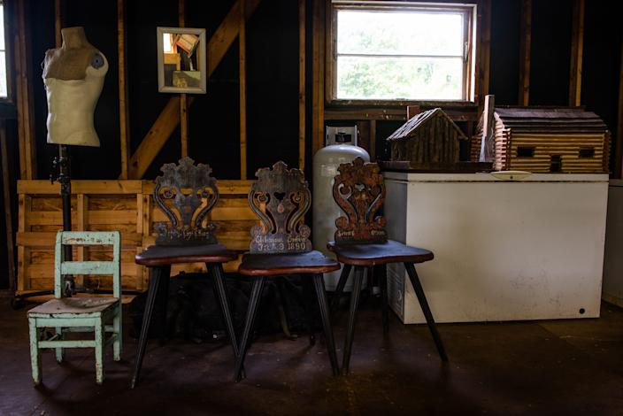 Antique chairs and log cabins stand on display in the barn of magazine editor Matt Hranek at his home in Hankins, NY on Friday, August 22nd, 2020.
