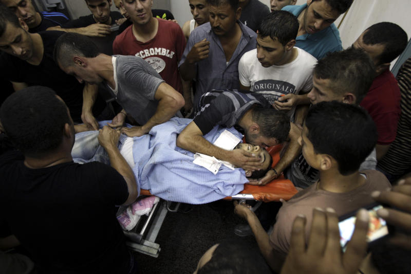 Relatives of Majd Lahlouh, 22, mourn over his body at a hospital in the West Bank town of Jenin, Tuesday, Aug. 20, 2013. Lahlouh was killed after Israeli soldiers came under fire during an arrest raid, the Israeli military said. (AP Photo/Mohammed Ballas)