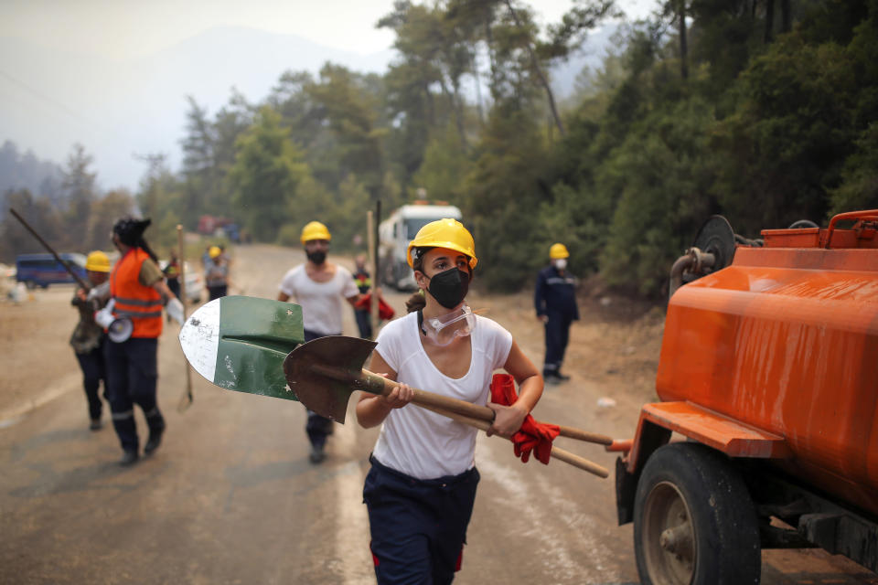 Turkish volunteers run as they fight wildfires in Turgut village, near tourist resort of Marmaris, Mugla, Turkey, Wednesday, Aug. 4, 2021. As Turkish fire crews pressed ahead Tuesday with their weeklong battle against blazes tearing through forests and villages on the country's southern coast, President Recep Tayyip Erdogan's government faced increased criticism over its apparent poor response and inadequate preparedness for large-scale wildfires.(AP Photo/Emre Tazegul)