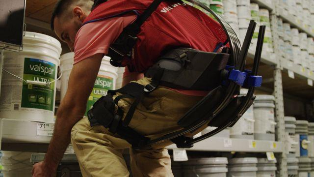 A Lowe's employee lifts a paint bucket while wearing an exo-suit as part of a pilot program in Virginia. (Quartz)