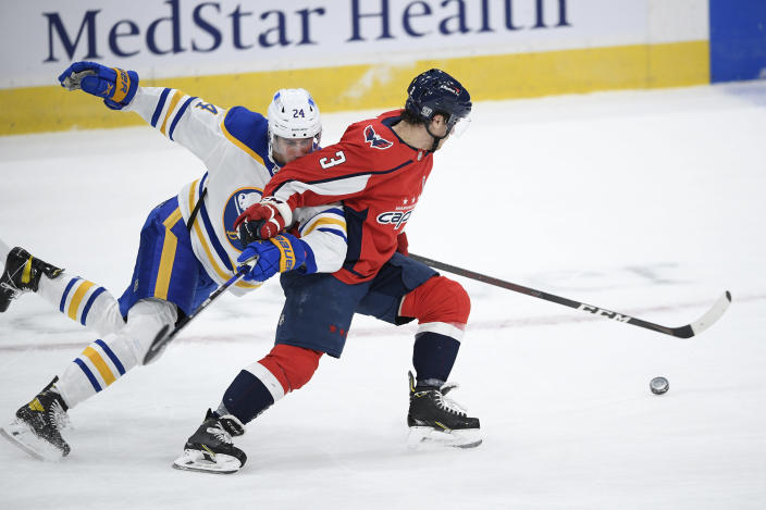 Washington Capitals defenseman Nick Jensen (3) and Buffalo Sabres center Dylan Cozens (24) chase the puck during the first period of an NHL hockey game, Friday, Jan. 22, 2021, in Washington. (AP Photo/Nick Wass)