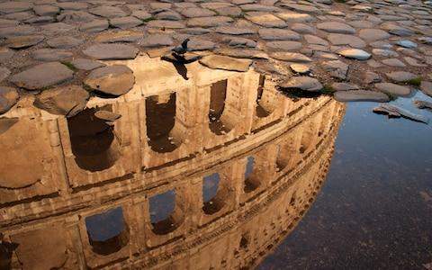 A puddle surrounded by sanpietrini cobbles reflects the Colosseum - Credit: Timothy Schultz