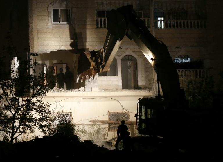 Israeli forces use a bulldozer to destroy two apartments that were home to the family of a Palestinian accused of the February killing of an Israeli woman in a pre-dawn operation in the flashpoint West Bank city of Hebron