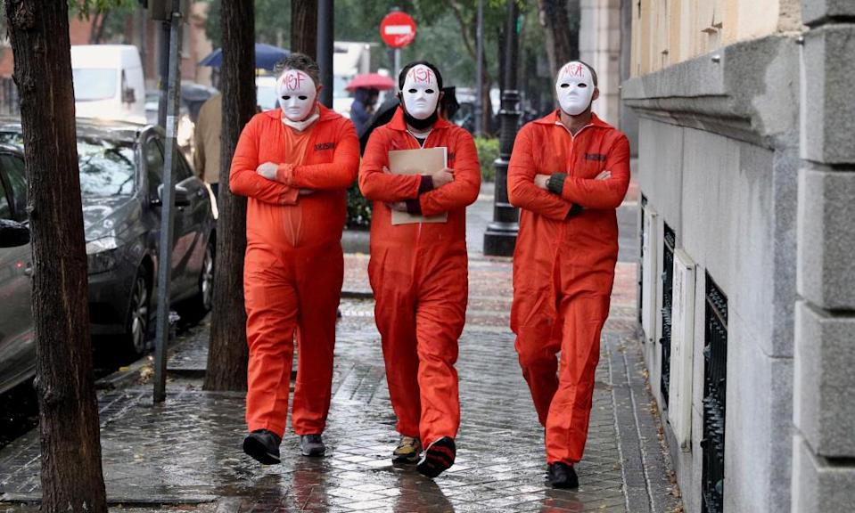 Three masked members of Madrid Without Future walk to hand in a request to support the restaurant and bar sector.