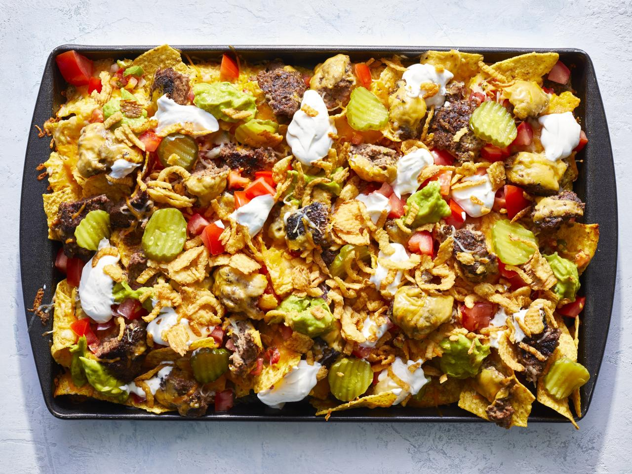 "<p>It was determined in our test kitchen that it is legitimately impossible to be anything other than happy while eating these cheeseburger nachos—do with that information what you will. The cookout-inspired food mashup is as perfect served as a fun, grilled snack for guests (especially during tailgating season) as it is an easy, throw-together meal to use up leftovers from a weekend get-together. So while the cheeseburger recipe provided here does produce an extremely moist and flavorful patty, you can certainly use leftover cooked burgers if you already have them on hand. Same idea applies to the nacho toppings; we went with a blend of typical Tex-mex toppers and backyard cookout accouterments, but you can vary things up however suits you. Your baking sheet will only be on the grill for a few minutes (just long enough for the cheese to melt) so you shouldn't experience any issues with the pan warping or taking on grill marks. However, for easy clean-up, you can certainly go ahead and wrap your pan in aluminum foil. </p> <p><a href=""https://www.myrecipes.com/recipe/grilled-cheeseburger-nachos"">Grilled Cheeseburger Nachos Recipe</a></p>"