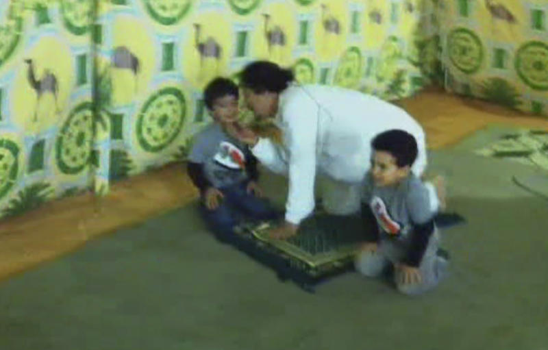 An image from an undated  32-second video, obtained Monday Sept 12 2011 by The Associated Press, which was found on a laptop in the home of Gadhafi's son Hannibal, showing Moammar Gadhafi clowning around with two young boys, presumably his grandsons, at an unknown location. The images of Gadhafi as a loving grandfather are in sharp contrast to the brutality of his 42-year regime, including the crackdown on opponents during Libya's six-month civil war. (AP Photo) TV OUT