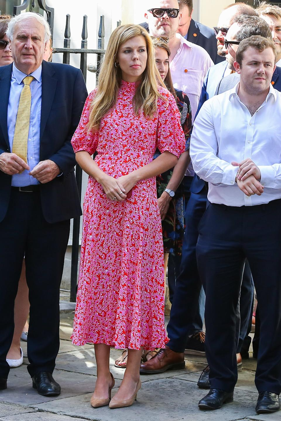 For her first public engagement, Carrie Symonds wowed in a £120 pink floral midi dress by British label, Ghost. Naturally, the dress sold out within minutes of her wearing it and Carrie even received the nod of approval from 'Good Morning Britain' presenter, Piers Morgan. <em>[Photo: Getty Images]</em>