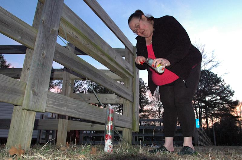 Gail Denny places a candle and stuffed animal outside the home of 9-year-old Savannah Hardin near Attalla, Ala., Wednesday, Feb. 22, 2012. Authorities say Hardin was forced to run for three hours as punishment for having lied to her grandmother about eating candy bars. The severely dehydrated girl had a seizure and her death days later was ruled a homicide. (AP Photo/Jay Reeves)