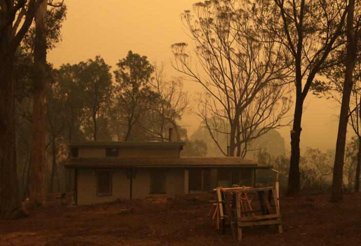 A mud brick house owned by Evan Harris where he is preparing to minimize fire impact at Burragate, Australia, Friday, Jan. 10, 2020, as a nearby fire threatens the area. Thousands of people are fleeing their homes and helicopters are dropping supplies to towns at risk of wildfires as hot, windy conditions threaten already fire-ravaged southeastern Australian communities. The danger is centered on Australia's most populous states, including coastal towns that lost homes in earlier fires. (AP Photo/Rick Rycroft)